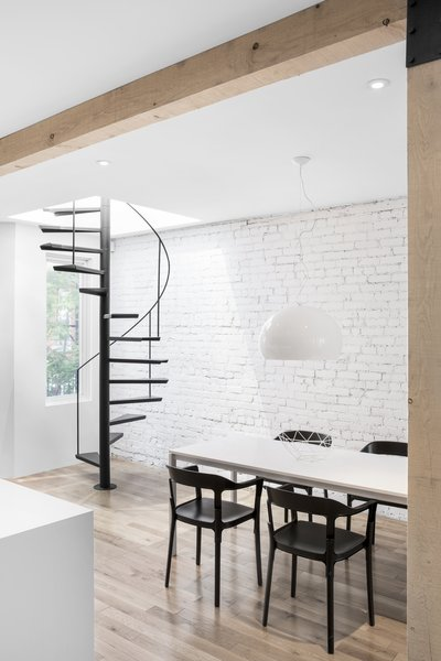 A formal dining space lies adjacent to the kitchen island.  A simple, white pendant light hangs above the black and white dining furniture.