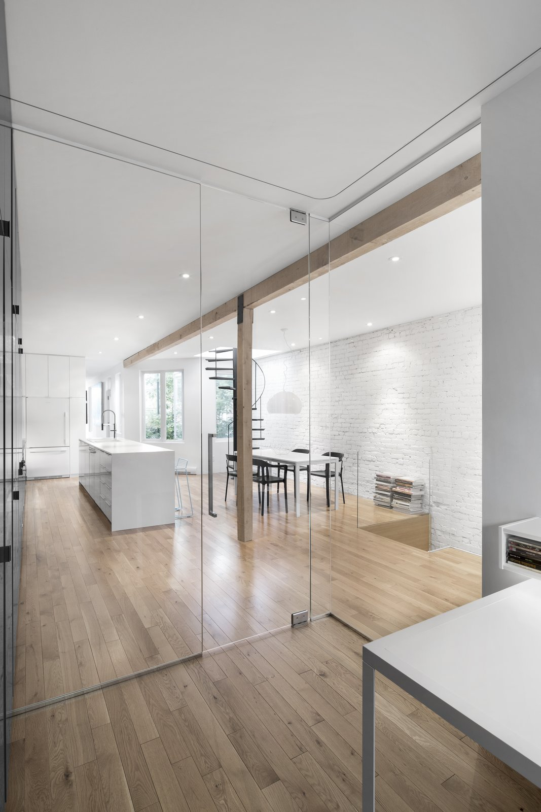 Glass walls allow light to filter through all spaces in the floor plan.  Continuous wood flooring blends from room to room, creating a coherent space.