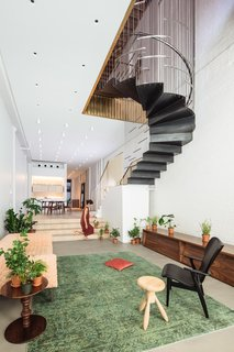 The stairs partially suspend from the ceiling above, allowing the living space to maintain its usable space and height.