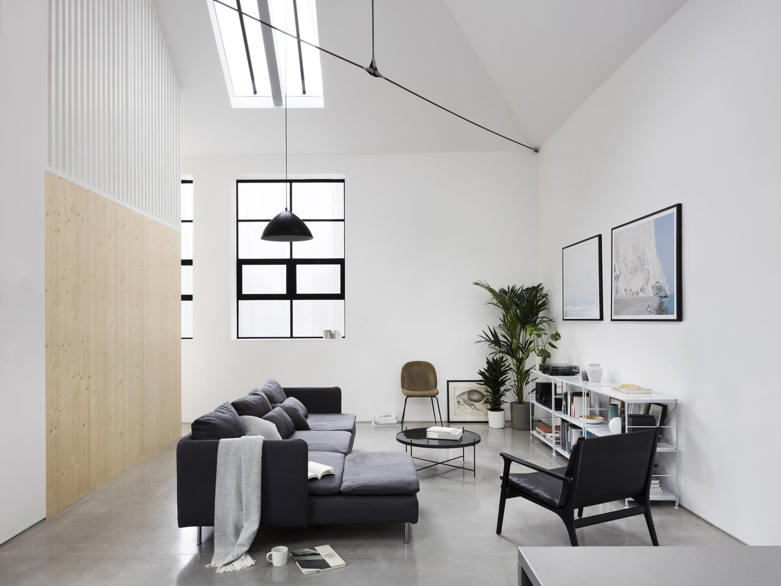 A large living space combines the best of all elements: exposed truss, steel framed windows, wood accents, simple pendant light,  and mod furnishings.