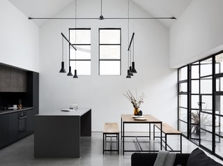 Large steel framed windows and doors frame the open kitchen and dining space.  Modern pendant lights hang above each cooking and eating surface.