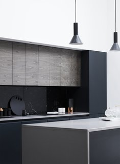 A black marble backsplash contrasts effortlessly with the white walls and light wood panels throughout the home.  Flat panel cabinets add an extra modern flair.