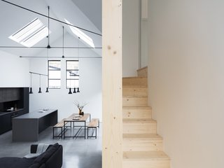 The wooden staircase winds its way between the living space and sleeping areas above.