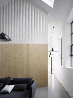The staircase is concealed between wood paneled walls adorned with white, wooden slats, allowing light to filter in while also creating a subtle division between spaces.
