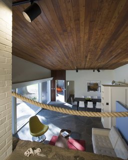 A stained cedar ceiling extends continuously over the living space.  The original rope railing remains intact.