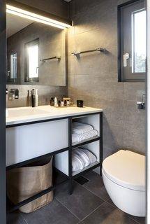 Small but efficient, the bathroom is completed with a vanity, storage, large mirror, and window.