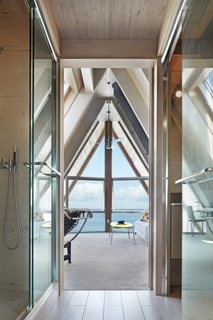 A full bath, framed by a glass shower enclosure and glass powder room enclosure, connects the two rooms on the third floor.  The openness between the spaces draws the bay views inward.