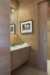 A floating wood vanity with a glass pedestal sink is a sleek solution in the main floor bath.  A wood pocket door conceals the water closet.