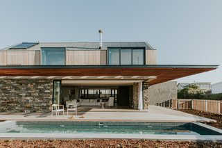 The large, sliding doors pocket into the deep stone walls, completely opening up the living space to the outdoors.