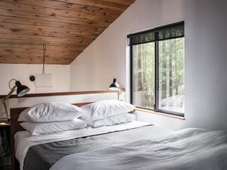At the head of the bed in the main bedroom, a half-height wall overlooks the dining space below.