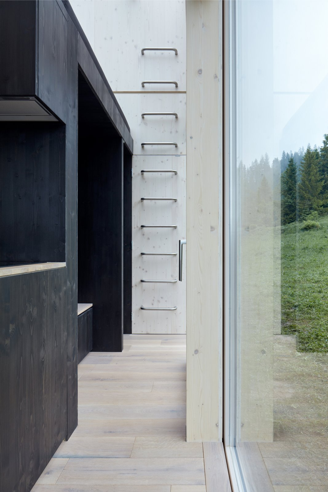 Hallway and Light Hardwood Floor Atop the kitchen and bathroom lies an additional sleeping quarter, directly under the sky above.  Photo 13 of 14 in This Off-Grid Prefab Cabin Boasts a Hidden Jacuzzi