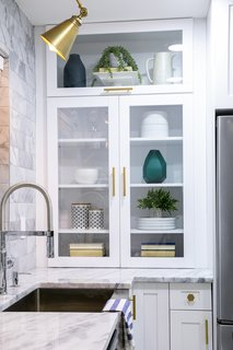 White shaker cabinets, some with glass inserts, combined with brass knobs and pulls, are a modern uptake on a simple style.