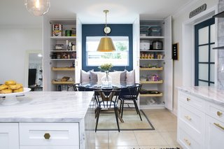 The custom built-ins create the perfect breakfast nook, complete with a built-in bench and pantry storage on both sides. A new window draws additional daylight into the space.
