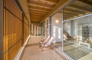 The in-between spaces between the walls of glass and the wooden shutters become exterior living spaces.