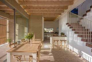 Light stone paving and wooden beams run continuously from interior to exterior, further blurring the boundary between the two.