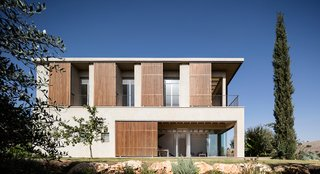 The movable shutters create a playful facade that conceals and reveals interior spaces.