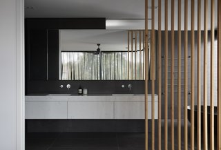 The master bath is a luxurious retreat wrapped in dark tiles and completed with a floating vanity and soaking tub.  The wood slats make an appearance, somewhat resembling the flowing curtains and surrounding trees in the background.