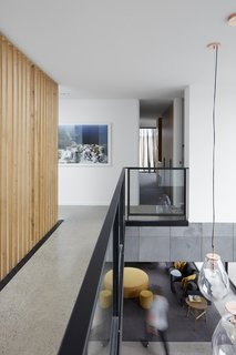 A catwalk, bordered by a modern steel-and-glass railing and a vertical wood-slat wall, connects the four bedrooms on the upper floor.