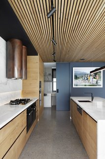 The copper hood makes a bold statement in the subdued kitchen.