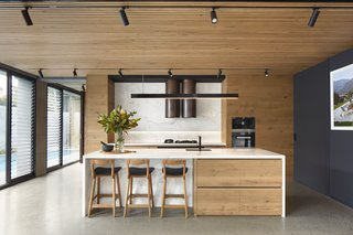 The kitchen is tucked under the living spaces above and wrapped in a warm wood finish.  The use of marble as a continuous countertop and backsplash creates a clean, contemporary look.