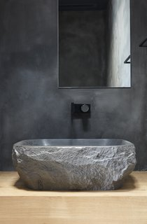 A custom wash basin from the stone supplier BAMSTONE emphasizes the home's connection to natural materials and the environment.