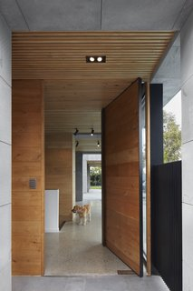 Wood accents, evident in casework, doors, and the wood-slat ceiling, provide warmth against the cool, bluestone facade.  A large wood-and-steel pivot door serves as a grand entry.