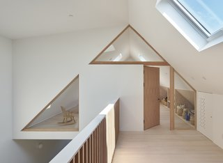 Wood framed glazing follows the slope of the gable above, referencing the original roof shape of the home.
