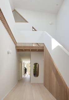 Douglas fir wooden slats follow the slope of the stairs and continuously wrap around as a guardrail, drawing the eye up and around.