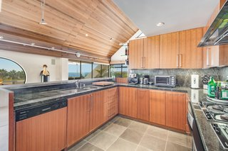 Emerald stone countertops and other rich materials create an ideal chef's kitchen with views to the ocean.