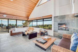 Windows wrap the corner of the home, providing continuous views from the hills to the ocean. The slate flooring extends upwards to wrap the fireplace.