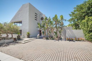 The white concrete exterior of the triangular home is enclosed by lush vegetation.  A courtyard welcomes guests upon entry.