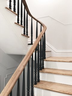 Stewart-Schafer finished the existing staircase and railings by hand.  All of the spindles are painted black to give the traditional formwork a modern aesthetic.