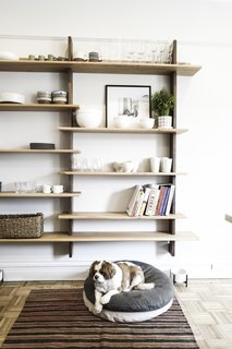 Custom built-in wood shelves provide a unique storage solution and a stylish design element in the kitchen.