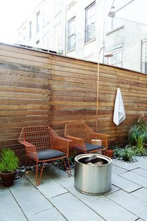 Not only does the backyard have colorful seating and a fire pit, but there is even an outdoor shower hidden by a wood slat fence.