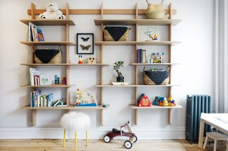 Custom built-in wood shelving adorns the playroom, providing a unique way to display books and toys.