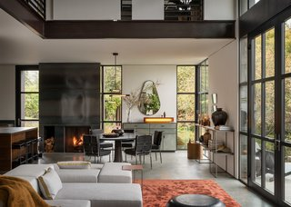A steel fireplace lies between the dining space and open kitchen.