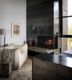 A vintage Mario Bellini club chair sits next to the hearth of the fireplace.