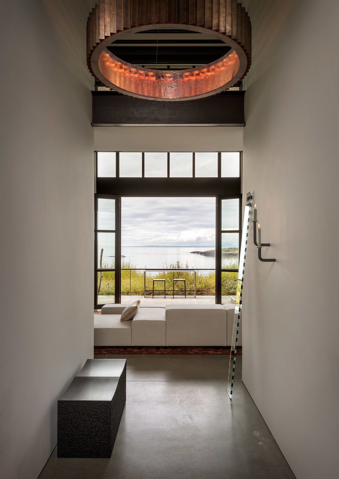 """Hallway and Concrete Floor Upon entry, John Eric Beyer's iconic block bench in blackened maple is revealed, adorned by a mirror piece, """"Seeing Glass"""", by artist Sabine Marcelis. And beyond, large openings display astounding views of the surroundings.   Photo 4 of 20 in Geremia Design Imbues an Olson Kundig Retreat With Warm Tones and Modern Art from False Bay Home and Writer's Cabin"""