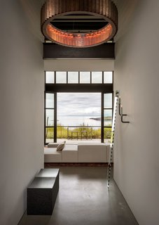 """Upon entry, John Eric Byer's iconic block bench in blackened maple is revealed, adorned by a mirror piece, """"Seeing Glass"""" by Sabine Marcelis and Brit van Nerven. And beyond, large openings display astounding views of the surroundings."""