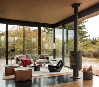 The cozy sitting area is an ideal writer's retreat.  Full-height glazing provides unobstructed views to the outdoors.  A rotatable fireplace allows the warmth to be enjoyed from either the inside or outside.