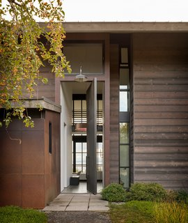 Olson Kundig's natural and warm architectural palette combines metal, wood, and concrete, set against the blues and greens of the lush surroundings and bay.