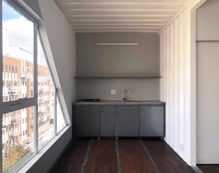 The shipping container walls have been painted white on the interior, creating bright living spaces.