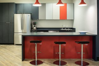 Simple Caesarstone countertops are accented by pops of color in the red bar, multi-tone cabinets, and pendant light fixtures by Troy.  Complete with Lez swivel bar stools, the break room is a great place to enjoy lunch or hold an informal meeting.