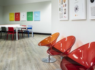 Bold colors in classic, modern furnishings create a fun work environment.  Red and orange Kartell chairs, Modway dining chairs, and a stylish Ping Pong table by RS Barcelona combine to create an energetic, multi-functional space.