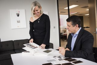 Kriste Michelini, founder of Kriste Michelini Interiors, and Sean Callahan, CEO of YDesign, consult on upholstery options.