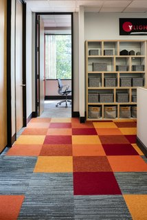 A custom pattern and color combination of FLOR carpet tiles adds variety to the flooring. Berlin shelving with Dorian bins adds functional storage.