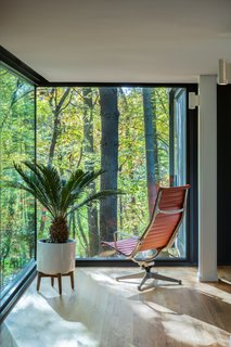 Glass corners create a seamless connection between the wooded landscape and interior living spaces.