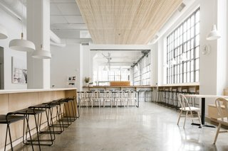 The open kitchen is the central hub of the office. It is a space to gather, take a break, and share ideas. Modern furnishings in molded black plywood and light ash tie in with the muted, industrial palette.