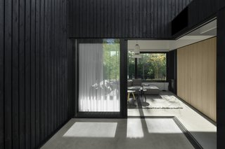 Large sliding glass doors open the living room up to the outdoors, blurring the boundary between inside and outside.