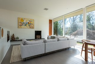 Large windows with automatic shades incorporate smart home technology, balancing daylight with comfort.